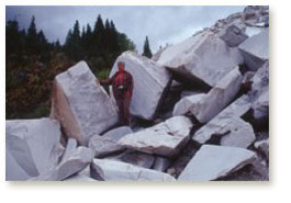 Sylvia stands amidst large blocks of marble
